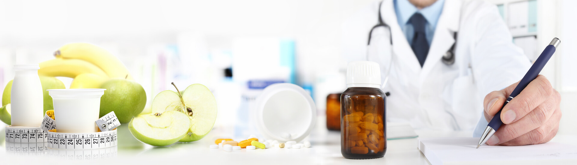 Apotheco - Nutritionist doctor writes the medical prescription for a correct diet on a desk with fruits, drugs and supplements