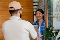 Beautiful latin american woman looking excited to receive a package delivered by postal worker